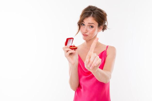 Очаровательная девушка в розовом платье с коробочкой с обручальным кольцом показывает палец на белом