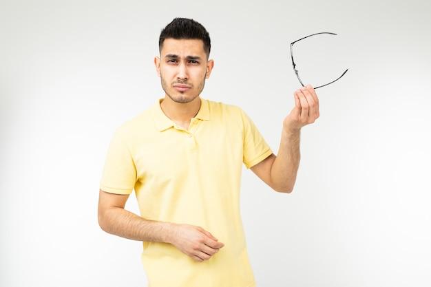 Парень чувствует боль в глазах, снимая очки для зрения на белом