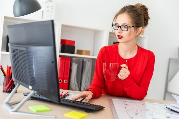 若い女の子が彼女のオフィスのテーブルに座って、コーヒーを手に持ってキーボードに印刷します。