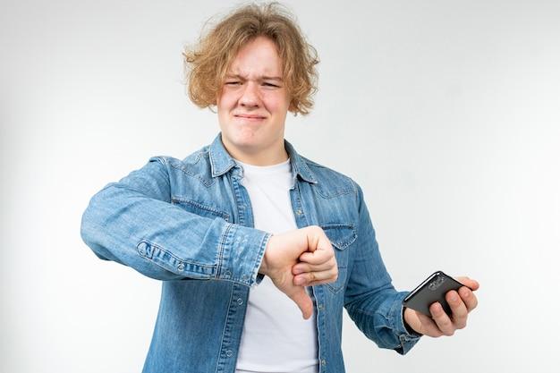 スマートフォンを手にしたデニムジャケットに金髪の男性ゲーマーが白に嫌い