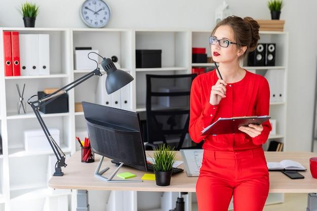 Молодая девушка стоит, опираясь на стол и держит карандаш и документы.