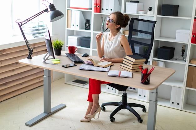 若い女の子がコンピューターの机に座って、開いた本と鉛筆を手に持っています。