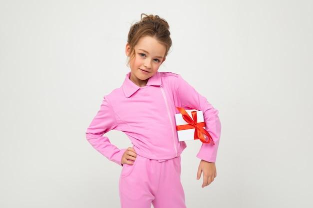 Девушка в розовой одежде держит подарочную коробку с красной лентой на белом с копией пространства