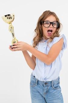 チャンピオンの女の子はコピースペースと白の優勝カップを保持します