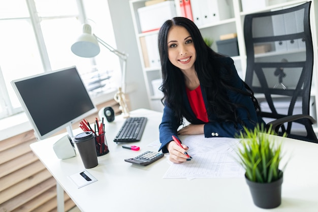 テーブルでオフィスで電卓とドキュメントを扱う美しい少女