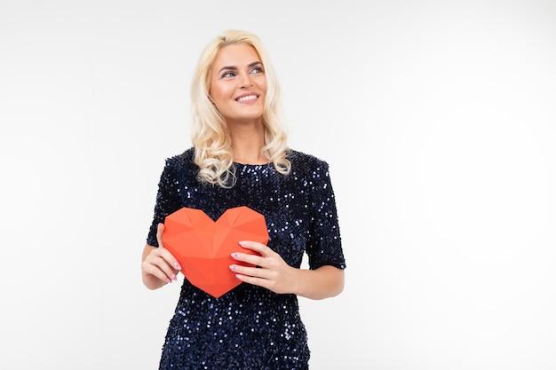 Белокурая молодая женщина в голубом платье держа бумажное красное сердце на белизне с космосом экземпляра