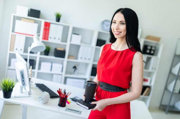 赤いスーツの美しい少女はオフィスに立って、ノートブックとコーヒーを保持しています。