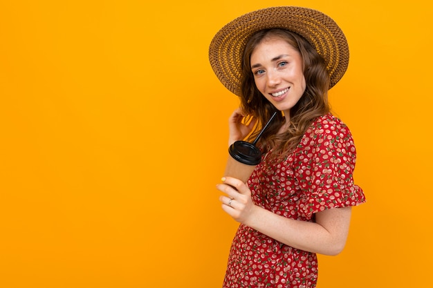 Туристическая девушка в соломенной шляпе в красном платье с бокалом охлаждающего напитка на желтом с копией пространства