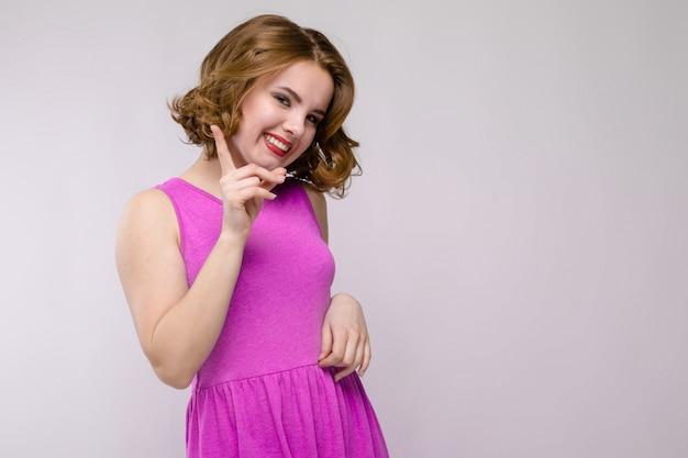 Очаровательная молодая девушка в розовом платье. молодая девушка показывает указательный палец