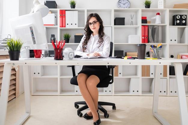 美しい少女は、オフィスのテーブルに座っています。