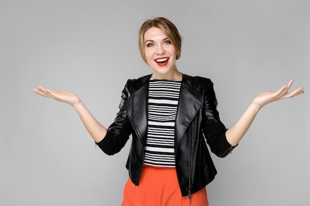 ストライプブラウスと開いている手を立って笑って笑っている革のジャケットで魅力的な若いブロンドの女の子
