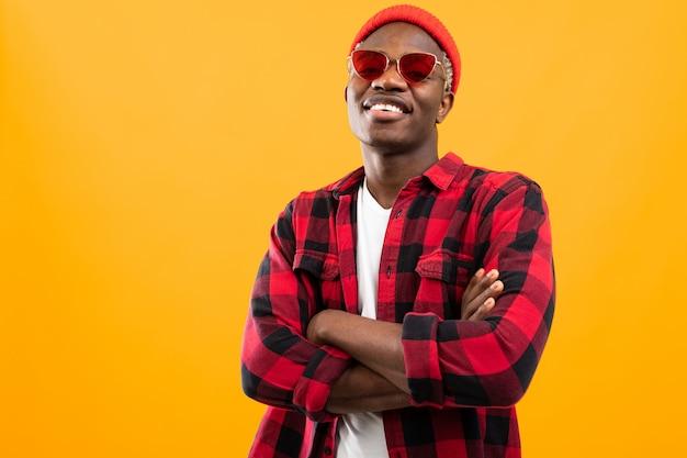コピースペースとオレンジ色の赤いレトロなメガネでスタイリッシュな笑みを浮かべて黒アフリカ人