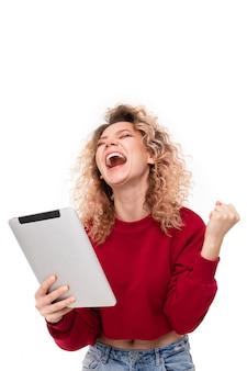 Эмоциональная кавказская девушка с вьющимися светлыми волосами в чате с друзьями и смех
