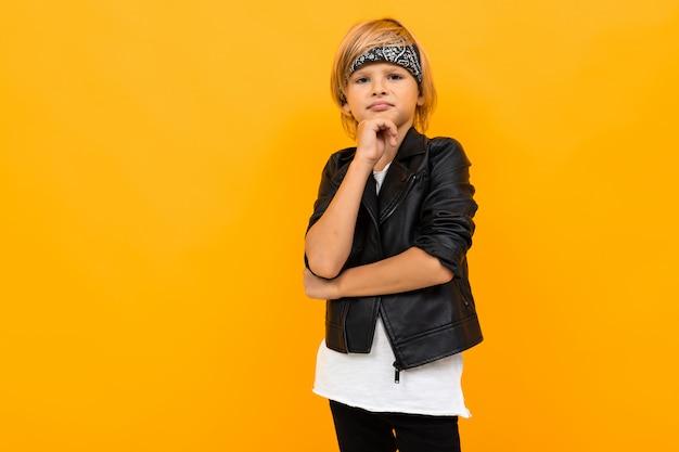 Стильный мальчик в черном пиджаке и белой футболке о чем-то думает