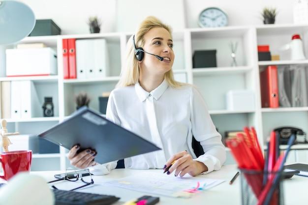 若い女の子がオフィスのデスクでマイクとヘッドフォンに座って、文書にメモを取ります。