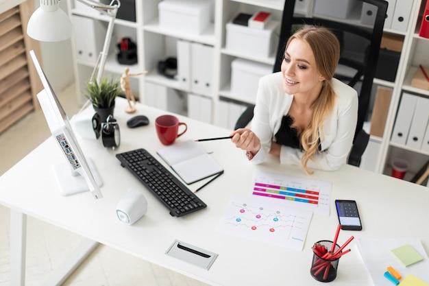若い女の子がオフィスのコンピューターデスクに座って、手に鉛筆を持ち、ドキュメントを操作しています。