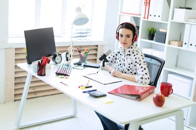 美しい少女は、ヘッドフォンとオフィスの机でマイクを使って座っています。