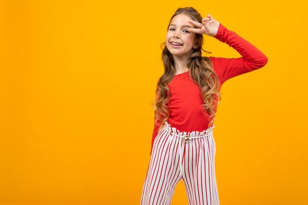Очаровательная девочка-подросток в красной блузке и полосатых брюках показывает эмоции на желтом с копией пространства