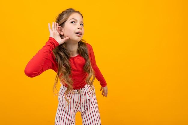 Девочка-подросток с вьющимися волосами в красной блузке и полосатых брюках слушает звуки, держа руки возле ушей на желтом с копией пространства
