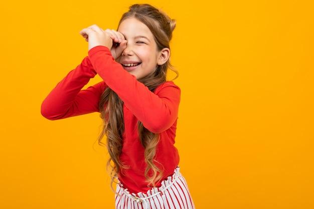 Удивленная девушка с вьющимися волосами в красной блузке и полосатых брюках высматривает что-то оранжевое с копией пространства