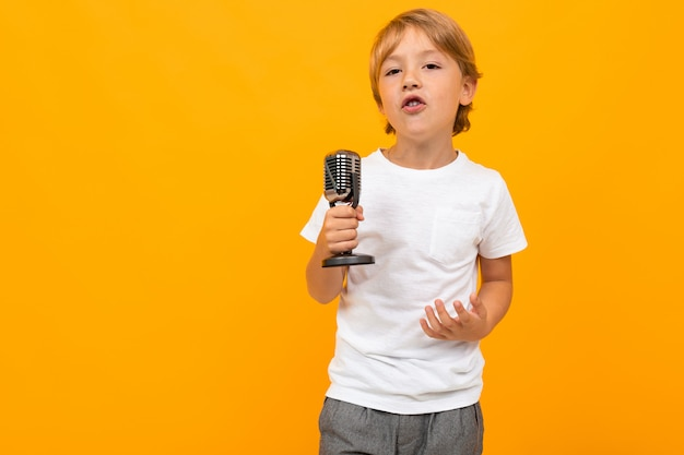 Белокурый мальчик с микрофоном на оранжевой стене студии