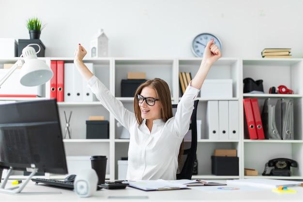 Молодая девушка сидит за компьютером стол в офисе и поднял руки вверх.