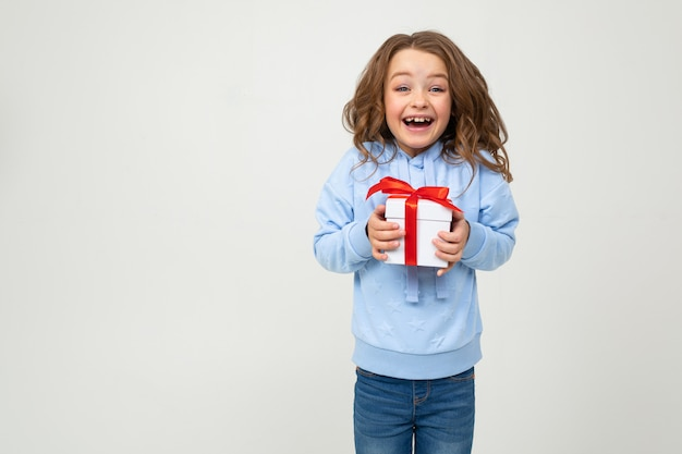 Удивленная девушка в синей одежде держит коробку с подарком с красной лентой на белой стене с пустым пространством