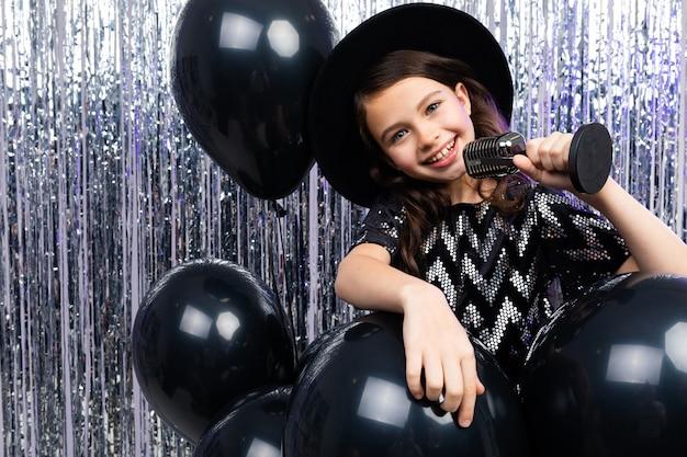 ヘリウム風船で光沢のある彼女の手にマイクを使って歌う黒いドレスの若いブルネットの歌手の肖像画