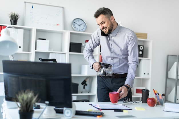 オフィスの若い男がテーブルの近くに立って、肩で電話を持ち、モニターを見て、カップにコーヒーを注いでいます。