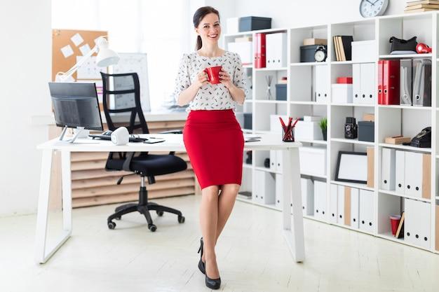 若い女の子がオフィスのコンピューターデスクに座って、赤いカップを保持しています。