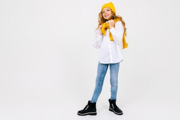 Стильная мечтательная кавказская девушка в белой рубашке и синих джинсах и желтой шляпе в сапогах позирует на белой стене