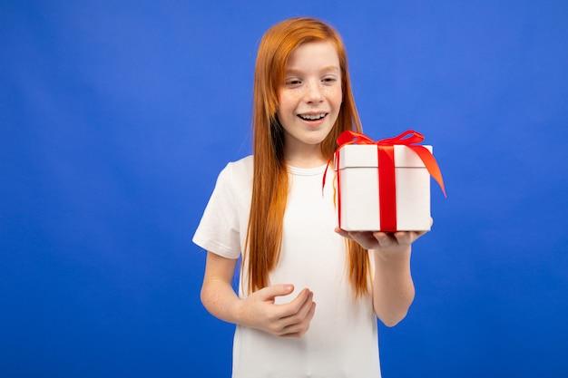 Счастливая девочка-подросток с рыжими волосами получила подарок на день рождения на синем фоне студии