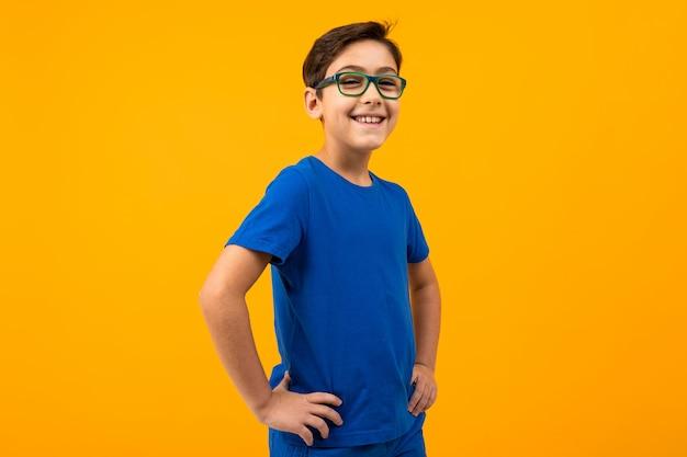 Мальчик в синей футболке в очках позирует на желтом фоне с копией пространства