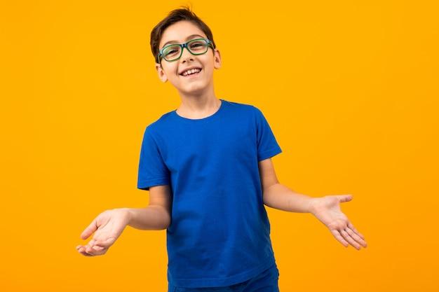 Красивый подросток мальчик в синей футболке в очках позирует на желтом фоне с копией пространства