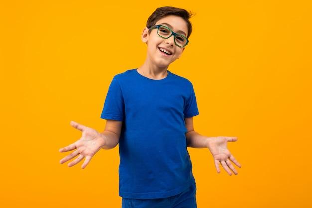 Красивый подросток мальчик в синей футболке в очках протягивает руки в разных направлениях на желтом фоне с копией пространства