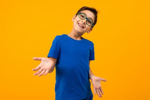 Красивый подросток мальчик в синей футболке с очками распространяет руки на желтом фоне с копией пространства