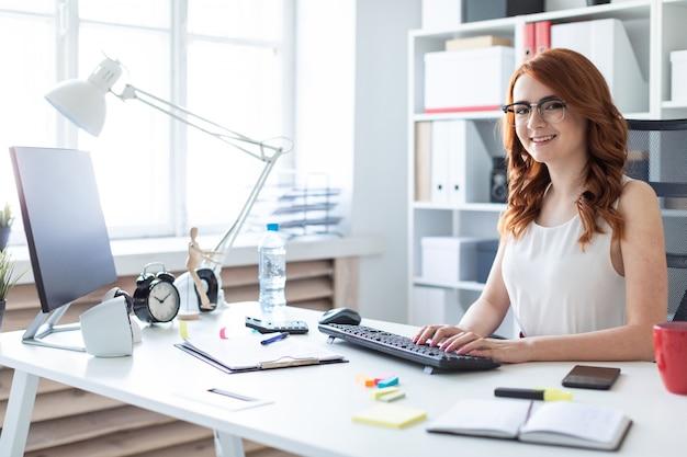 美しい少女は、オフィスの机に座って、キーボードで入力します。