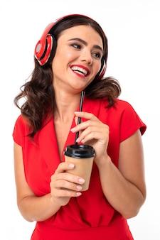 スタイリッシュなサングラスと赤いドレスの魅力的な女の子は、白い背景で音楽を聴いて楽しんでいます