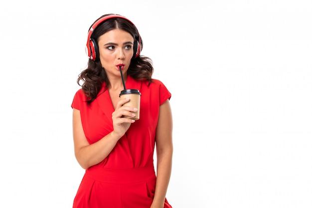 素敵な白人少女の肖像画はイヤホンで音楽を聴くし、白い背景で隔離のコーヒーを飲む