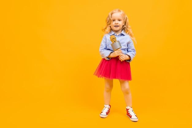 Маленькая белокурая девушка с микрофоном на оранжевой предпосылке с космосом экземпляра