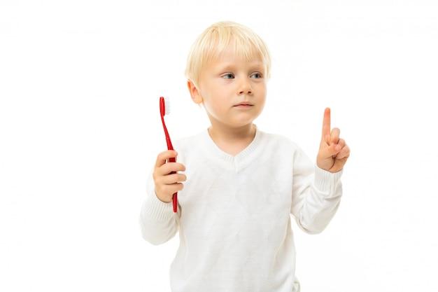 Довольно маленький мальчик с короткими светлыми волосами и голубыми глазами с красной зубной щеткой, фотография на белом фоне