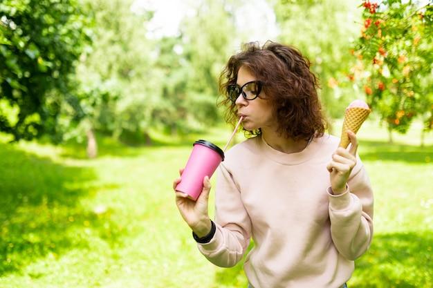 Привлекательная студентка с чашкой кофе и мороженым гуляет в парке во время обеденного перерыва
