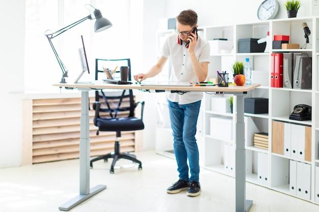 メガネの若い男がコンピューターの机の近くに立って、電話で話しています。彼の前には、磁気ボードとマーカーがあります。首に、男のヘッドフォンがかかっています。