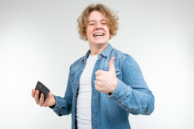 彼の手にスマートフォンを持つデニムジャケットのブロンドの髪を持つ男性のゲーマーは、白い背景のようなショー