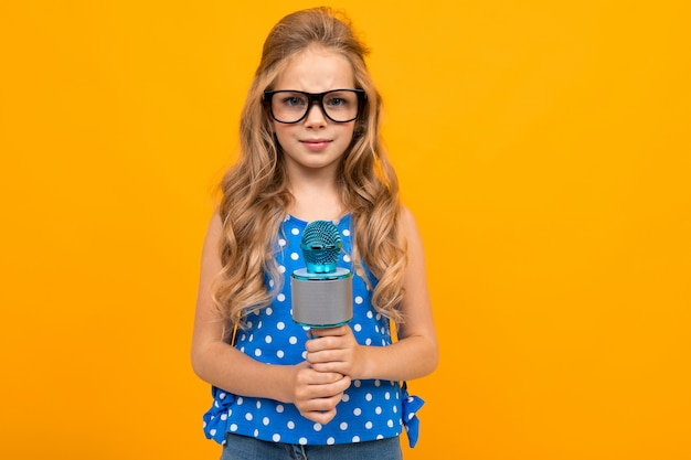 Девушка в очках держит микрофон на оранжевом фоне