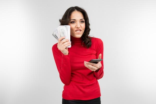 Брюнетка держит свою зарплату в руках на белом фоне с копией пространства