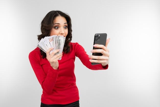 Брюнетка девушка делает селфи с деньгами в руках на белом фоне с копией пространства