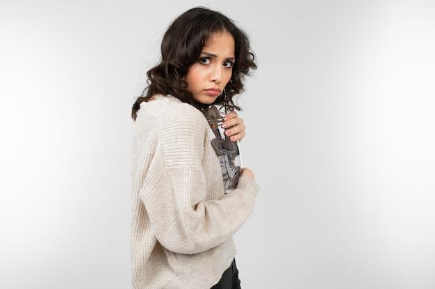 女の子は彼女の貯金箱をしっかりと抱擁し、それが灰色の背景に奪われないようにします