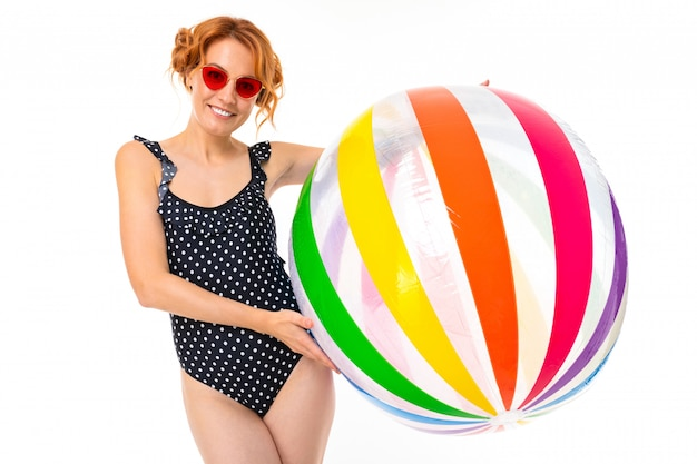 レトロな黒のワンピース水着と白地に水のための縞模様のボールとサングラスで魅力的な女の子