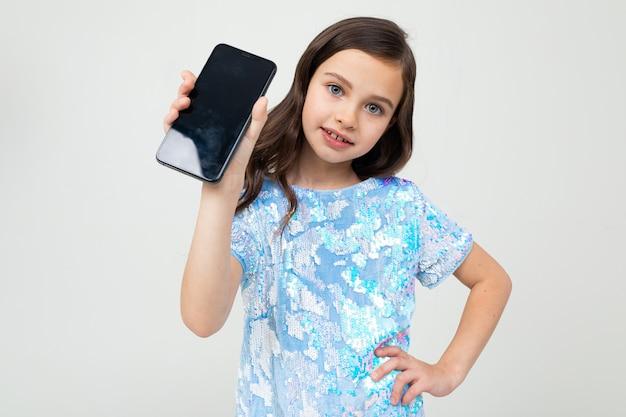 若い女の子は白い背景のレイアウトで空白の画面を示しています